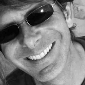 Zwart/wit foto van Arnout Mostert met zonnebril op en vrolijke brede glimlach.